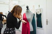 Mulher usando pinos para anexar tecido vermelho ao manequim ao fazer vestido no estúdio alfaiate profissional — Fotografia de Stock