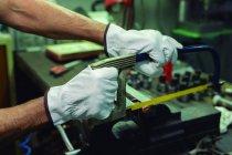 Mains gantées d'un réparateur professionnel anonyme sciant des détails métalliques avec une scie à métaux pendant le travail en usine — Photo de stock