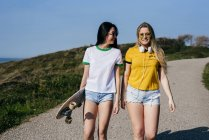 Trendy teen girls with long board in sunshine — Stock Photo