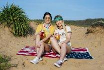 Модные девушки с напитками на пляже — стоковое фото