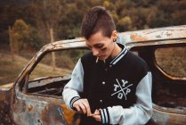 Молода жінка з коротким волоссям і розфарбованим обличчям, запалюючи цигарку, стоїть біля старої іржавої машини в сільській місцевості. — стокове фото