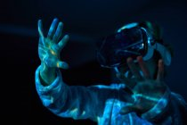 Boy wearing virtual glasses at home in dark with light effects and shadow — Stock Photo