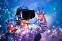 Elementary age kid wearing virtual glasses at home with colored light effects — Stock Photo