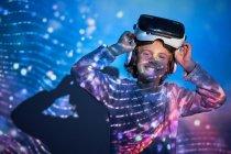 Kind mit virtueller Brille zu Hause mit farbigen Lichteffekten, Blick in die Kamera — Stockfoto
