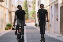 Веселий афроамериканець дивиться на фотоапарат і їде на електричному скутері, а чорний хлопець дивиться вгору і їде на велосипеді на вулиці. — стокове фото