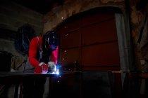 Блексміт працює у своїй майстерні з електричним зварювачем. — стокове фото