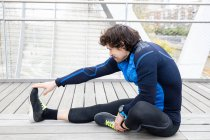 Vista lateral do corredor masculino em roupas de treino sentado no chão de madeira da ponte fechada e realizando exercícios de alongamento das pernas — Fotografia de Stock