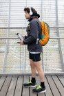 Бічний погляд на чоловічого бігуна в теплих куртках і шортах з рюкзаком, що стоїть в закритому мосту з термос пляшкою і мобільним телефоном. — стокове фото