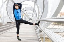 Jogger standing on boardwalk and performing basic stretching exercises on bar at river bank at daytime — Stock Photo