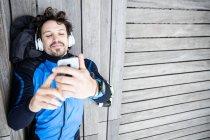 Von oben junger borstiger Sportler mit Kopfhörern, die auf Holztreppen der Uferpromenade liegen und SMS per Handy — Stockfoto