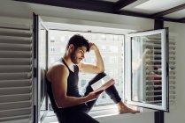 Side view of young serious handsome man in casual sleeveless shirt sitting on window and reading interesting book — Stock Photo