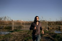 Hombre de pelo largo con barba en camisa y jeans huyendo de la ciudad por la puerta y mirando a la cámara durante el día - foto de stock
