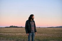 Man with long hair and beard standing in middle of field at dusk and looking away with concern — Stock Photo
