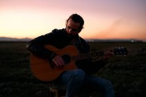 Bearded guitarist with long hair sitting in meadow at sunset holding musical instrument and playing tune in hands while pensively looking away — Stock Photo