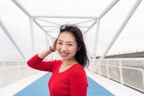Mulher asiática encantadora em camisa vermelha sorrindo e olhando para a câmera enquanto caminhava na ponte da cidade moderna — Fotografia de Stock