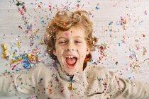 Menino bonito com rosto coberto de confete — Fotografia de Stock
