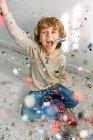 Garoto muito feliz se divertindo com confete em casa — Fotografia de Stock