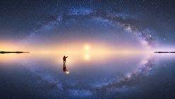 Силует анонімного чоловіка, що стоїть на поверхні води і тягнеться до зоряного барвистого нічного неба молочним шляхом. — стокове фото