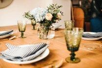 Сверху букет разноцветных цветов и зеленых цветочных веток в вазе с водой на деревянном столе, накрытом на обед — стоковое фото