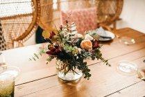 Сверху букет разноцветных цветов и зеленых цветочных веток в вазе с водой на деревянном столе, накрытом на стол для еды с красивым ротанговым стулом на заднем плане — стоковое фото