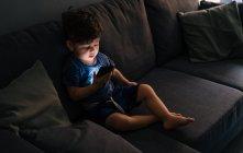Curieux petit garçon naviguant smartphone à la maison — Photo de stock