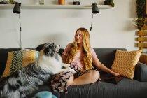 Позитивная босиком женщина с планшетом улыбается и гладит милый Колли, сидя на удобном диване дома — стоковое фото