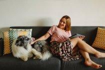 Mujer descalza positiva con la tableta sonriendo y acariciando lindo Collie mientras está sentado en cómodo sofá en casa - foto de stock