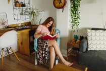 Seitenansicht einer barfüßigen Frau, die auf einem Stuhl sitzt, während sie zu Hause im gemütlichen Wohnzimmer ein Buch liest — Stockfoto