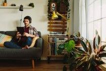 Бічний погляд людини на навушники, що переглядають планшет і слухають музику на столі, відпочиваючи на зручному дивані вдома. — стокове фото