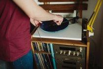 Vista lateral recortada de una persona irreconocible en ropa casual poniendo un disco de vinilo en el tocadiscos antes de escuchar música en una acogedora habitación en casa - foto de stock