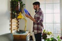 Вид сбоку на молодого человека в повседневной одежде, который кладет виниловую пластинку на поворотный стол перед прослушиванием музыки в уютной комнате дома — стоковое фото