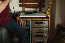 Перед тим як слухати музику вдома в затишній кімнаті, нерозбірливий одяг кладе на стіл вінілові пластинки. — стокове фото