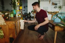 Vue latérale de l'homme pieds nus assis sur des hanches et cueillette disque de vinyle de l'étagère dans une chambre confortable à la maison — Photo de stock