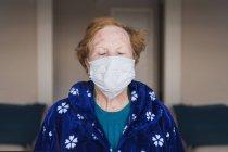 Старша жінка з рудим волоссям у синьому одязі та медичній масці, яка дивиться на камеру, стоячи у лікарняній палаті. — стокове фото