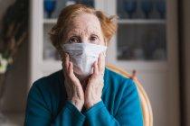 Mujer mayor con el pelo rojo en bata azul y máscara médica mirando a la cámara mientras está de pie en la habitación del hospital - foto de stock