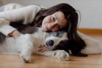 Cuidar a la hembra en suéter de lana abrazando divertido perro Border Collie mientras yacen en el suelo de madera juntos mirando a la cámara - foto de stock