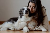 Одяг жінки в шерстяному светрі обіймаючи веселий прикордонний собака Коллі, лежачи на дерев'яній підлозі, дивлячись на камеру. — стокове фото