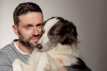 Мужчина в повседневной одежде обнимает и целует любимого пса Пограничной Колли, пока он смотрит в камеру — стоковое фото