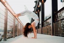 Vista lateral de ángulo bajo de la mujer flexible en sujetador deportivo y polainas que realizan soporte de mano de escorpión mientras se ejercita descalzo y se apoya en la barandilla de metal en la ciudad - foto de stock