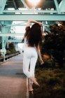 Jovem magro mulher em esportes top e leggings de pé descalço no passeio freio e levantando o braço graciosamente na cidade à noite — Fotografia de Stock
