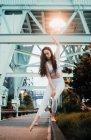 Junge, schlanke Frau in Sporttop und Leggings steht barfuß auf dem Bürgersteig und hebt anmutig den Arm in der Abendstadt — Stockfoto