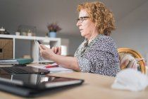 Side view of focused adult woman in casual clothes and eyeglasses using smartphone in earphones while sitting at table and working on laptop at home — Stock Photo