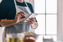 Side view of cropped female in apron browsing smartphone and searching for recipe while standing in light home kitchen — Stock Photo