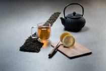 Aromatic beverage in glass mug and teapot arranged with lemons and heaps of dried tea leaves on table on black background — Stock Photo