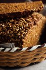 Closeup of tasty cut bread with brown crust and crunchy sunflower seeds on top in wicker basket — Stock Photo