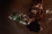 З висоти лагідної самиці з закритими очима і в одязі лежить на підлозі біля скляної пляшки в кімнаті з сонячним світлом. — стокове фото