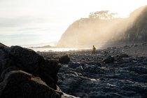 Viaggiatore anonimo in giacca gialla calda che cammina sulla costa di pietra grezza circondato da gravi scogliere alla luce del sole — Foto stock