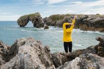 Vista posteriore turista donna irriconoscibile in giacca gialla calda in piedi sulla spiaggia rocciosa e alzando le braccia mentre ammira viste sul mare — Foto stock