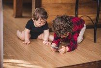 Adorable garçon naviguant smartphone tout en étant assis sur le sol près de petit frère à la maison — Photo de stock