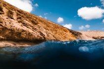 Basso angolo di acqua di mare limpida lavaggio scogliera rocciosa sulla costa sotto il cielo blu con nuvole — Foto stock